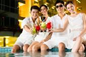 Čínské páry pití koktejlů v baru u bazénu hotelu