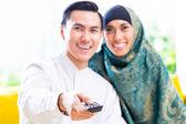 Asijské muslimský pár přepínání Tv s dálkovým ovládáním
