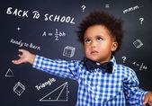 Ritratto di scolaro afroamericano riccio intelligente nella scuola sulla lezione di matematica, risolvere compito vicino alla lavagna