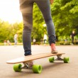 Постер, плакат: Girl practicing urban long board riding