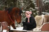 Teenager girl sitting in the sled with furs and brown horse