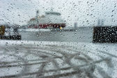 Ship in the port through the raindrops on glass in a strong snow
