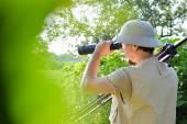 čas prohlídky Safari: obrázek turistické nebo zkoumání vědce, muž v dřeň helmu baví pozorovat ve zvětšení rozsahu při pohledu letní slunečný den zelené lesy  sky copy prostoru pozadí portrét