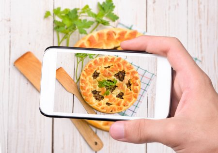 Hands taking photo mushroom pie with smartphone
