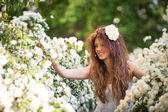 Okouzlující mladá dáma s krásným úsměvem na jaře zahrady plné bílé květy