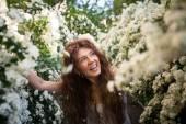 Krásná mladá dáma s legrační úsměv na jaře zahrady plné bílé květy