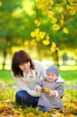 Giovane madre con il suo piccolo bambino nel parco dautunno