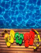 Multicolor flip-flops on wooden planks against blue water background. Summer family vacation concept