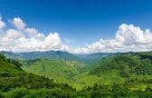 Zelené hory a modrou oblohu s mraky