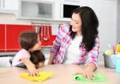 Dcera a matka čištění kuchyňského stolu