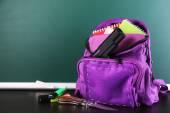 Zbraň ve školní batoh na dřevěný stůl, na tabuli pozadí