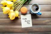 Cup of coffee with fresh cupcake, tulips and Happy Monday massage on wooden background