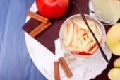 Glas und Karaffe Apfelschorle mit Früchten und Gewürzen auf Tisch hautnah