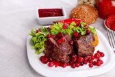 Gustosi arrosti di carne con salsa di mirtilli su piatto, su sfondo chiaro
