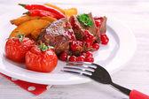 Gustosi arrosti di carne con salsa di mirtilli e verdure arrostite sulla piastra, su fondo di legno di colore