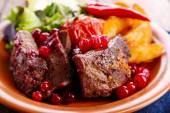 Lecker gebratenes Fleisch mit Cranberry-Sauce, Salat und gebratenes Gemüse auf Teller, Nahaufnahme