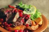 Lecker gebratenes Fleisch mit Cranberry-Sauce, Salat und gebratenes Gemüse auf Platte auf Sackleinen Hintergrund