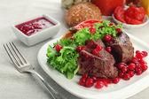 Lecker gebratenes Fleisch mit Cranberry-Sauce auf Teller, auf hellem Hintergrund