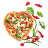 Tasty heart shaped pizza decorated with hot peppers and basil isolated on white background