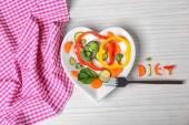 Užitečné nakrájíme zeleninu na desce v podobě srdce na dřevěný stůl pohled shora