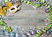 Sfondo di carnevale colorato con ghirlande, stelle filanti, cappellini da festa, coriandoli e maschera