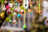 Několik velikonočních barevné vejce visí na větvi stromu