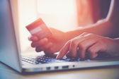 Ruce držící kreditní kartu a pomocí přenosného počítače. Online nakupování