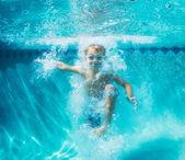 Mladý chlapec, potápění pod vodou v bazénu