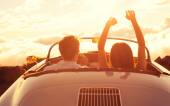 Young Couple Wathcing the Sunset in Vintage Sports Car