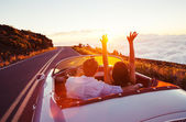 Guidare verso il tramonto. Romantic Young Couple Enjoying Sunset Drive in automobile sportiva dellannata classica