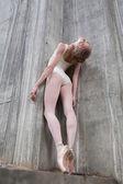 Schlanke Tänzerin auf einem Hintergrund des Betons