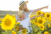 Beautiful woman with son in sunflower field