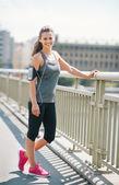 Usmívající se žena běžec s růžové boty na mostě