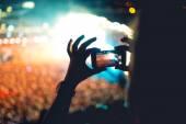 Silueta muže pomocí smartphone aby video na koncertě. Moderní životní styl s bederní s obrázky a videa na místní koncertu. Hlavní zaměření na kamery a osvětlení