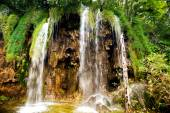 Breathtaking view of natural waterfall, lake cascade and water in deep tropical forest.