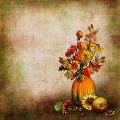 Background with autumn leaves, berries in a vase from pumpkin