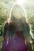 Bella donna bionda in un campo di grano al tramonto
