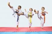 Három gyermek karategi vert rúgás láb előre