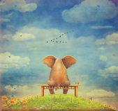 Smutný slon sedící na lavičce na glade