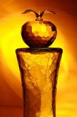 Glass apple on broken cylinder in yellow light