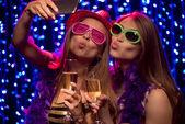 Due belle giovani donne con bicchieri di champagne fare selfie al partito nel randello di notte