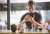 Mladý muž sleduje tabletu v kavárně
