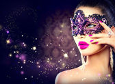 Donna sexy che indossa la maschera di Carnevale sopra priorità bassa scura di vacanza