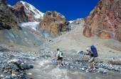 Two hikers crossing mountain river
