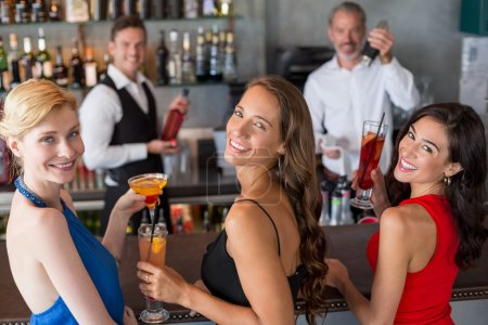 Happy female friends holding glass of cocktail at bar counter