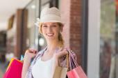 Usmívající se žena drží nákupní tašky