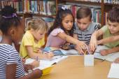 Žáci pracují společně u stolu v knihovně