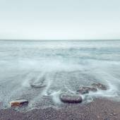 Minimalist misty seascape with rocks at long exposure