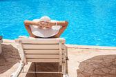 Žena v bílém klobouku leží na lehátku u bazénu