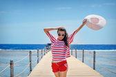Fiatal nő tele energiával egy ponton, a tengerparton, egy napsütéses napon a